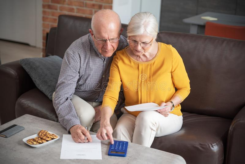 Senior couple paying bills together. With calculator. Couple doing some paperwork and calculations at home stock photography