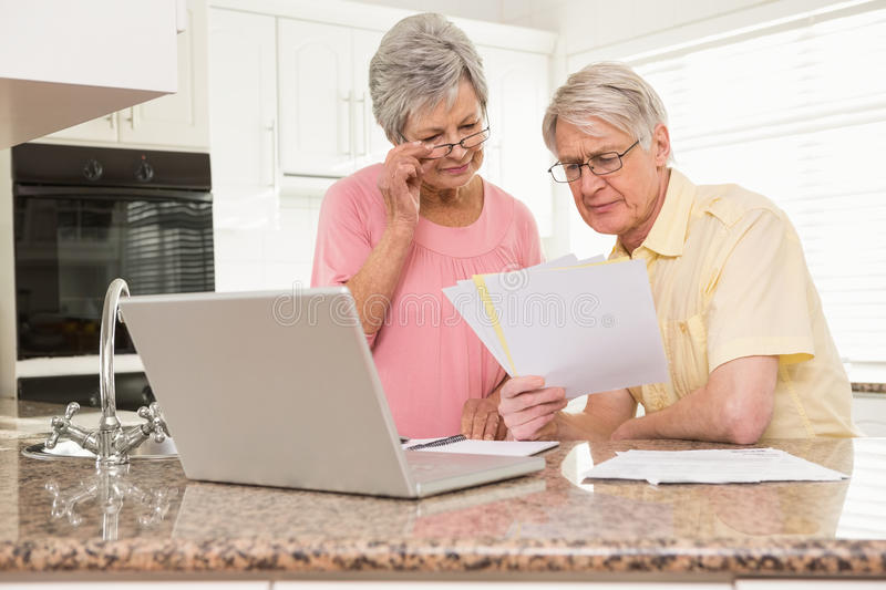 Senior couple paying their bills with laptop. At home in the kitchen royalty free stock photo