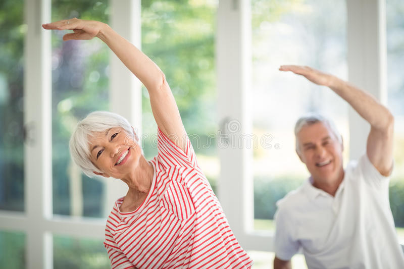 Senior couple performing stretching exercise at home royalty free stock photos