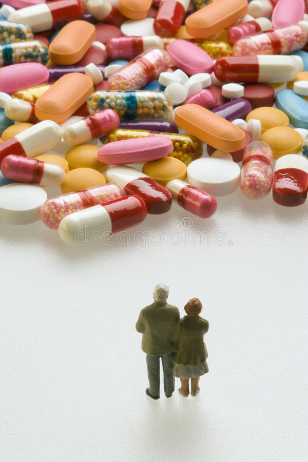 Senior couple with pills. Miniature couple standing in front of capsules and pills royalty free stock photo