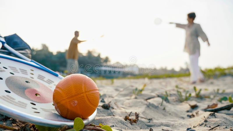 A senior couple plaing tai chi ball game with racket and ball on the foreground. Taiji baloon ball concept. A senior couple plaing tai chi ball game with racket royalty free stock photography