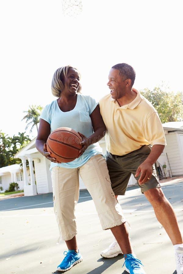 Senior Couple Playing Basketball Together royalty free stock photography