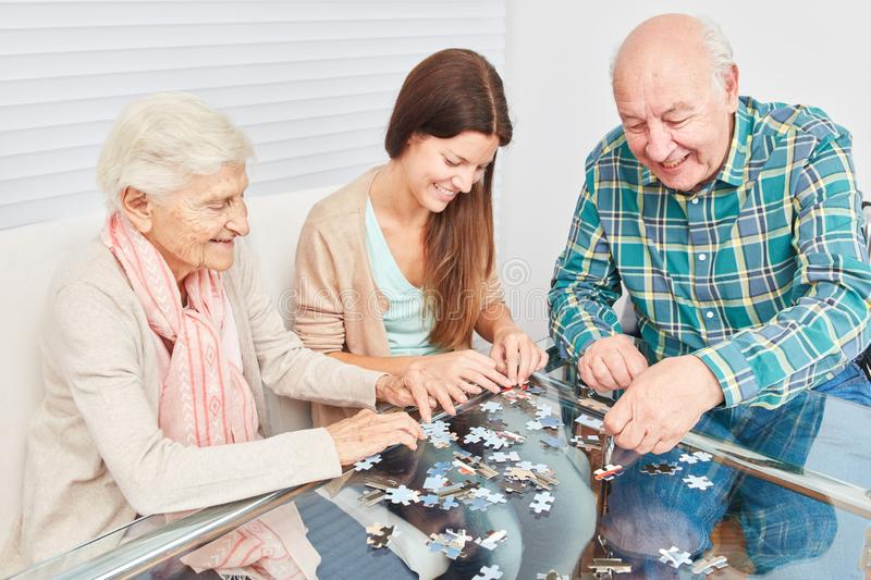 Senior couple playing jigsaw puzzle against dementia stock images