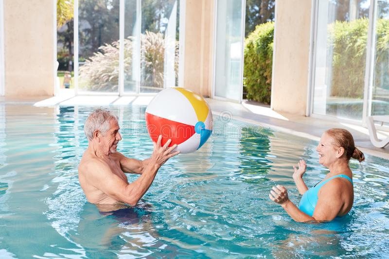 Senior couple plays water polo in the spa stock photo