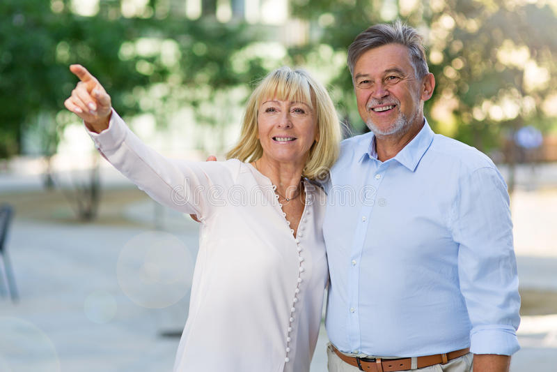 Senior couple pointing. Loving Senior Couple Outdoors Smiling stock images