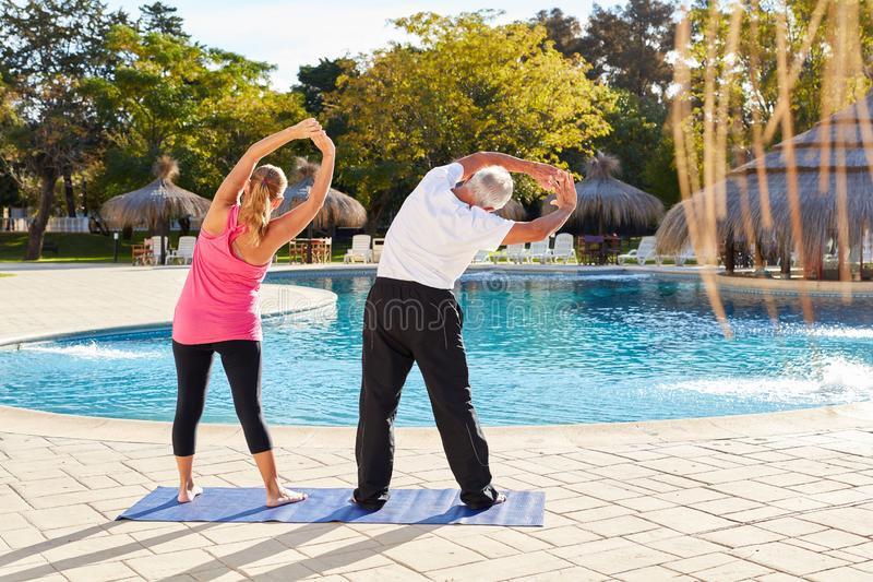 Senior couple at the pool is doing stretching stock photo