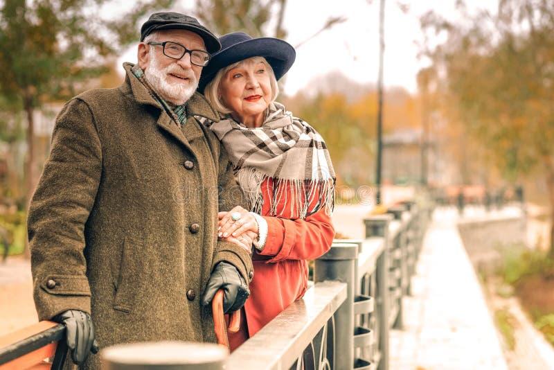 Senior couple posing on a bridge in autumn stock images