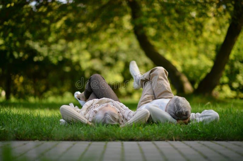 Senior couple posing in park lying on grass stock photo