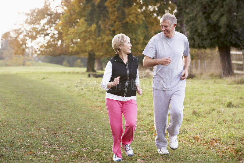 Senior Couple Power Jogging In The Park royalty free stock image