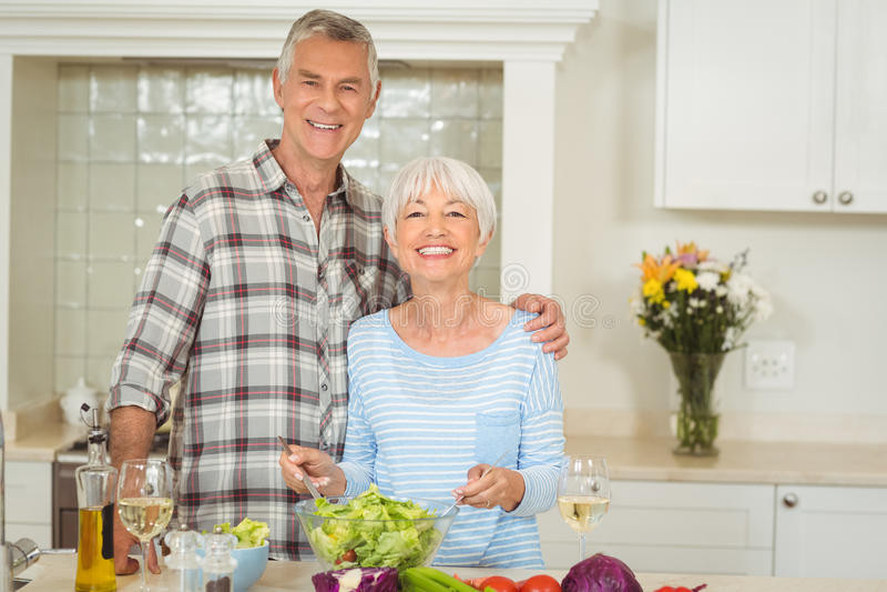 Senior couple preparing vegetable salad royalty free stock photography
