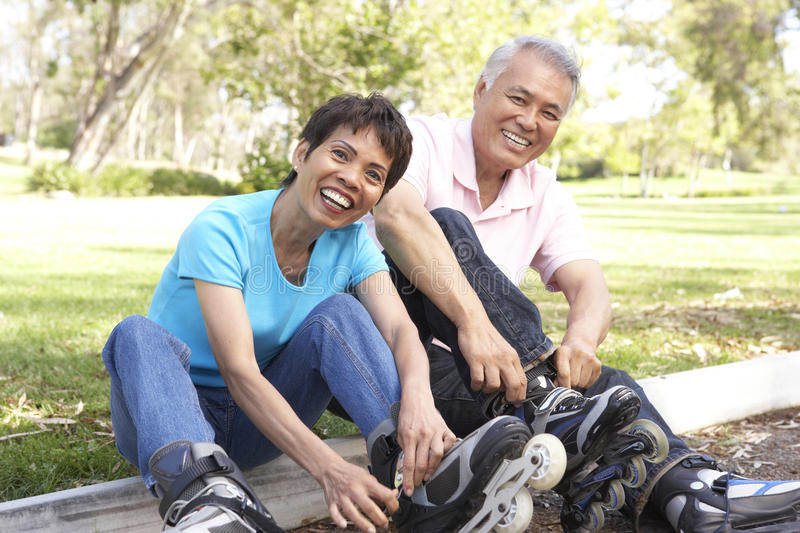 Senior Couple Putting On In Line Skates In Park stock photos