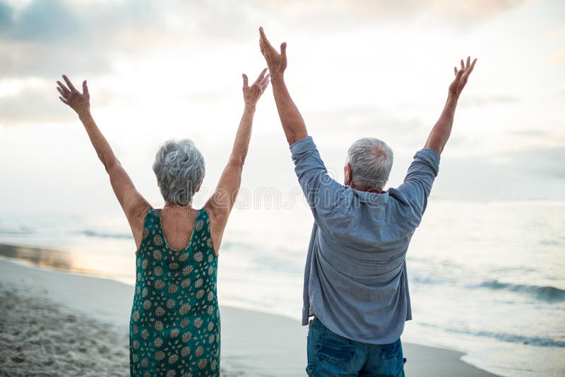 Senior couple raising their arms royalty free stock image