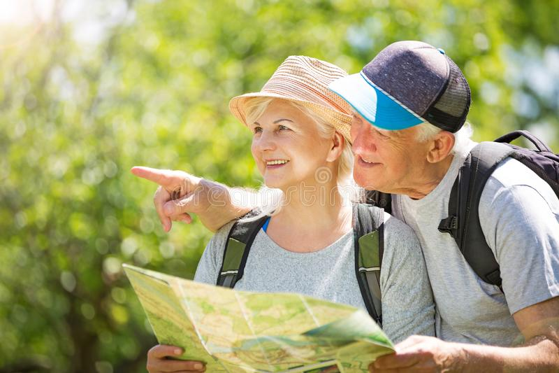 Senior couple reading map on country walk. Smiling happy elderly seniors couple stock images