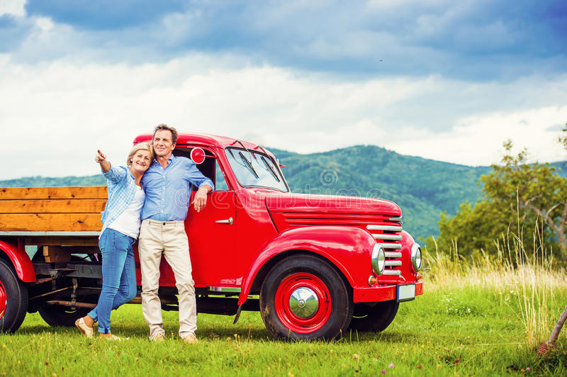 Senior couple with red car. Senior couple standing by their vintage red car royalty free stock image