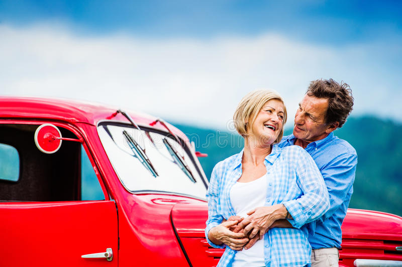 Senior couple with red car royalty free stock photography