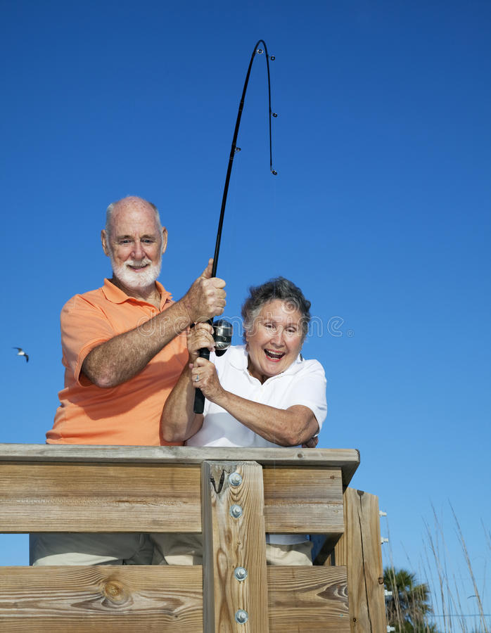 Senior couple reel in fish stock image image of fishing for Florida fishing license for seniors