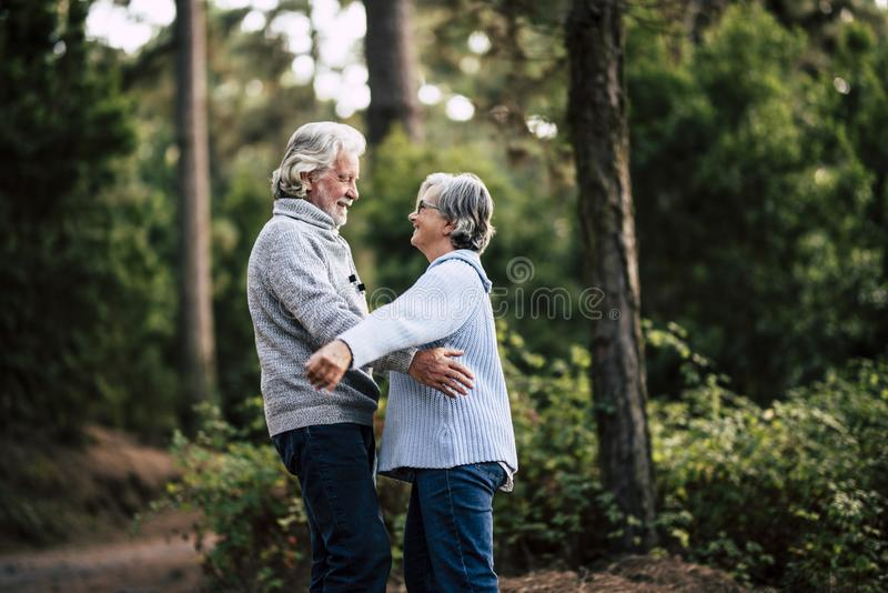 Senior couple in relationship and love hug together in outdoor leisure activity in the forest nature - old people forever together royalty free stock photography