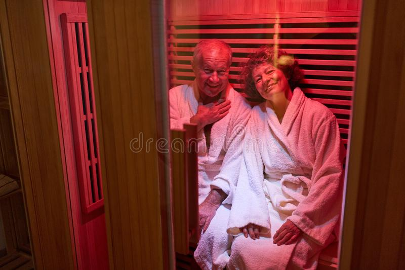 Senior couple relaxes in the steam sauna royalty free stock photography