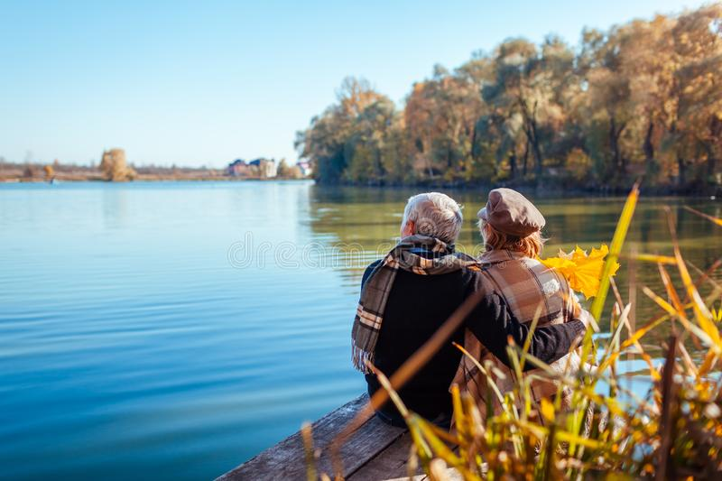 Senior couple relaxing by autumn lake. Happy man and woman enjoying nature and hugging sitting on pier stock photography
