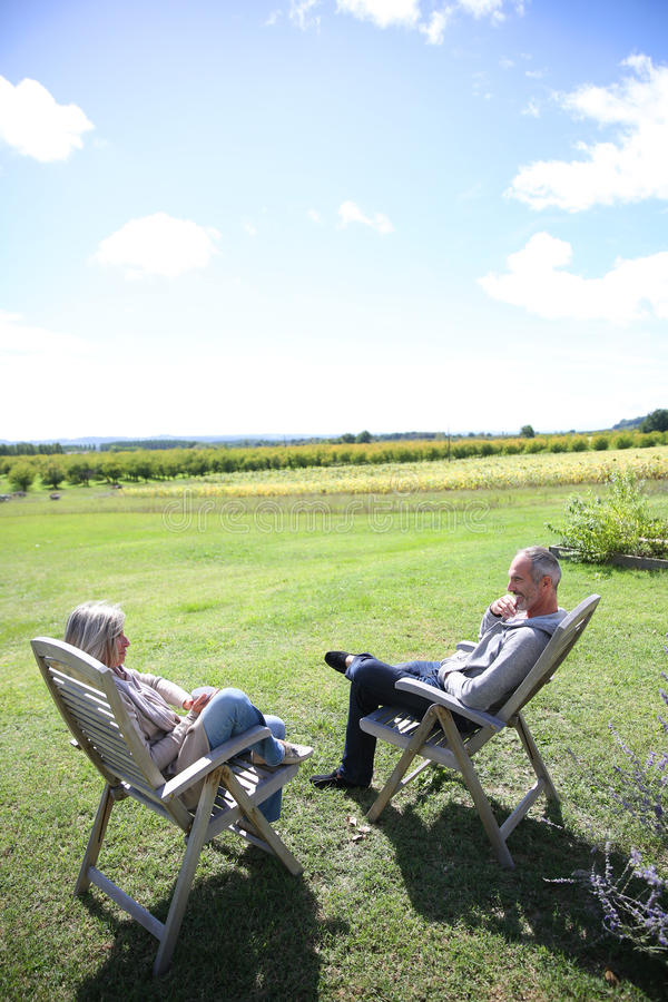 Download Senior Couple Relaxing In Chairs On Sunny Day Stock Image - Image: 33885101