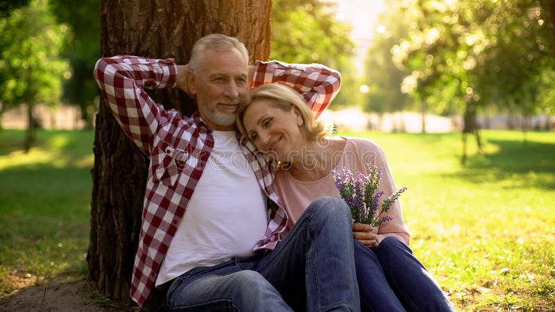 Senior couple relaxing on grass in park and enjoying romantic date, true love royalty free stock images