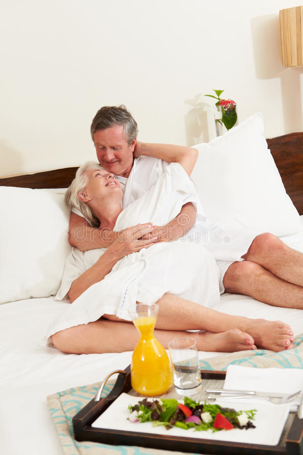 Senior Couple Relaxing In Hotel Room Wearing Robes stock photos