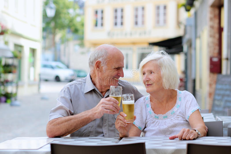 Senior couple relaxing on outdoors cafe. Happy couple of seniors, a men and his wife, are enjoying glass refreshing drink sitting at the open air terrace of cozy stock photos