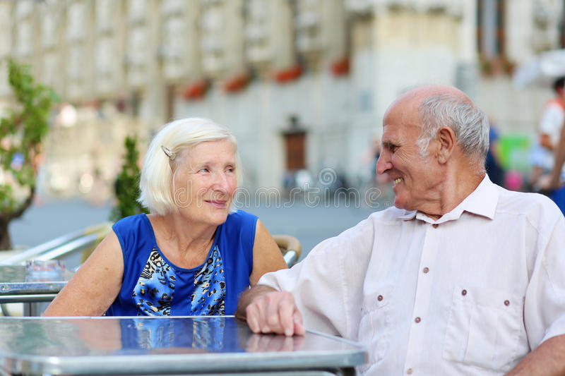 Senior couple relaxing on outdoors cafe. Happy couple of seniors, a men and his wife, are enjoying glass refreshing drink sitting at the open air terrace of cozy royalty free stock photography