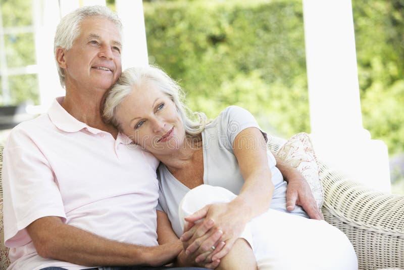 Senior Couple Relaxing On Seat Outside House stock photo