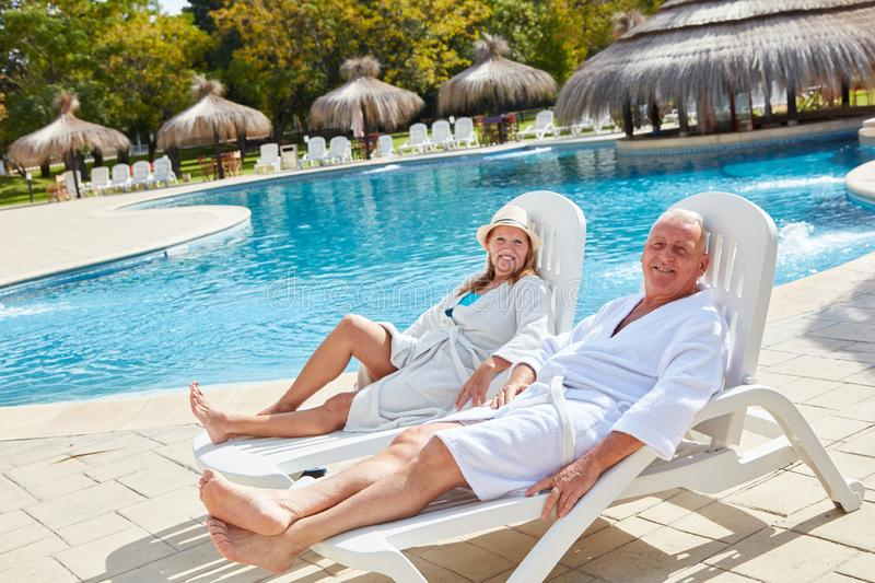 Senior couple relaxing by the swimming pool stock photography