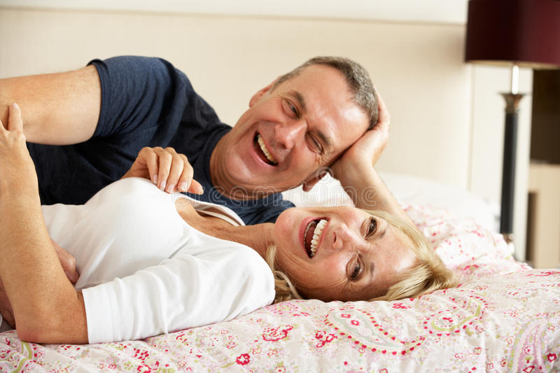 Download Senior Couple Relaxing Together In Bed Stock Photo - Image of couple, affectionate: 26616286
