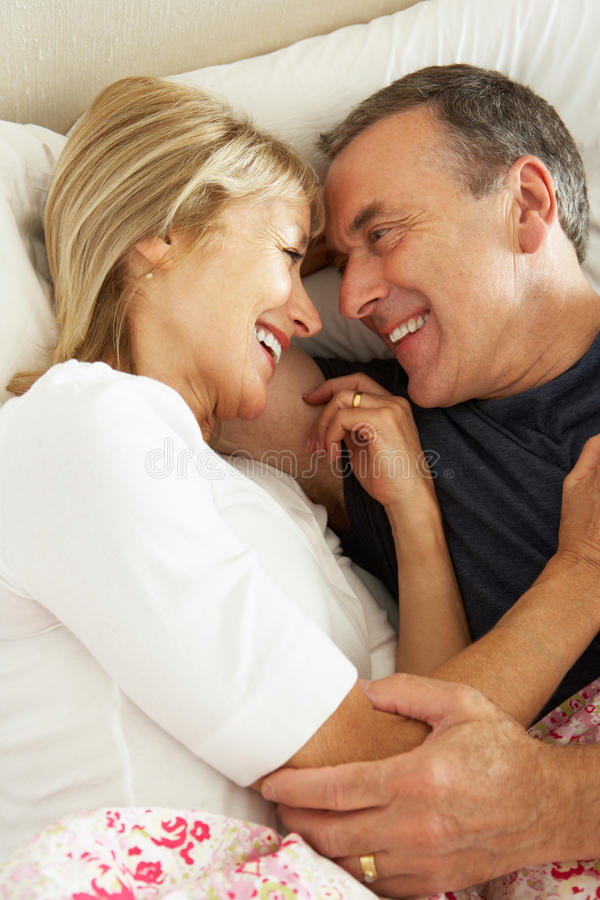 Download Senior Couple Relaxing Together In Bed Stock Photo - Image: 26616300