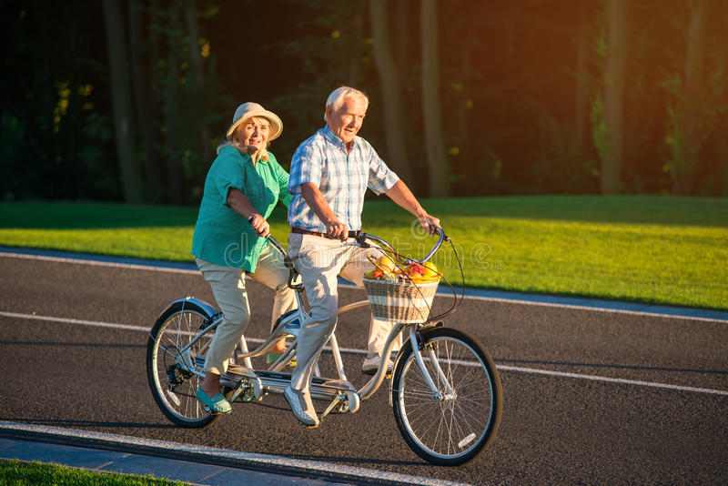 Senior couple rides tandem bike. royalty free stock photos