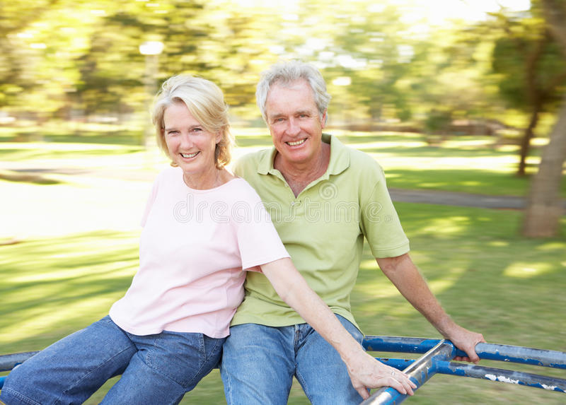 Download Senior Couple Riding On Roundabout In Park Stock Image - Image: 14639885