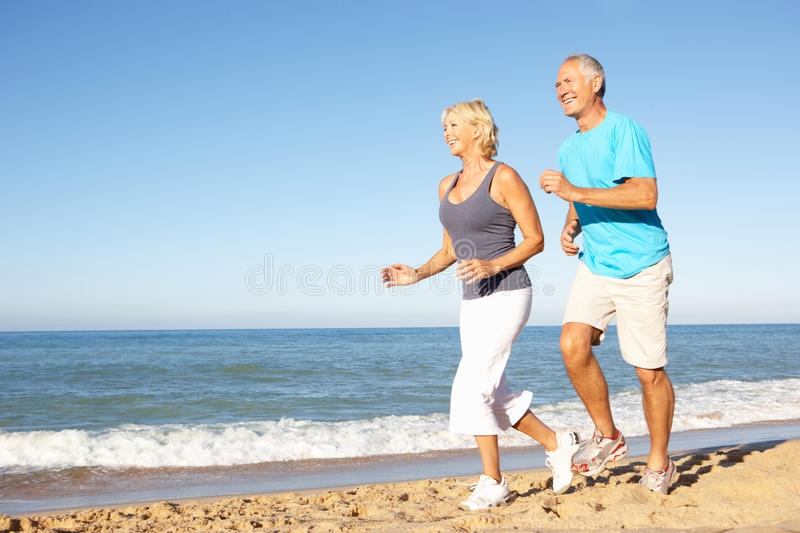 Download Senior Couple Running Along Beach Stock Image - Image of couple, exercising: 16614891