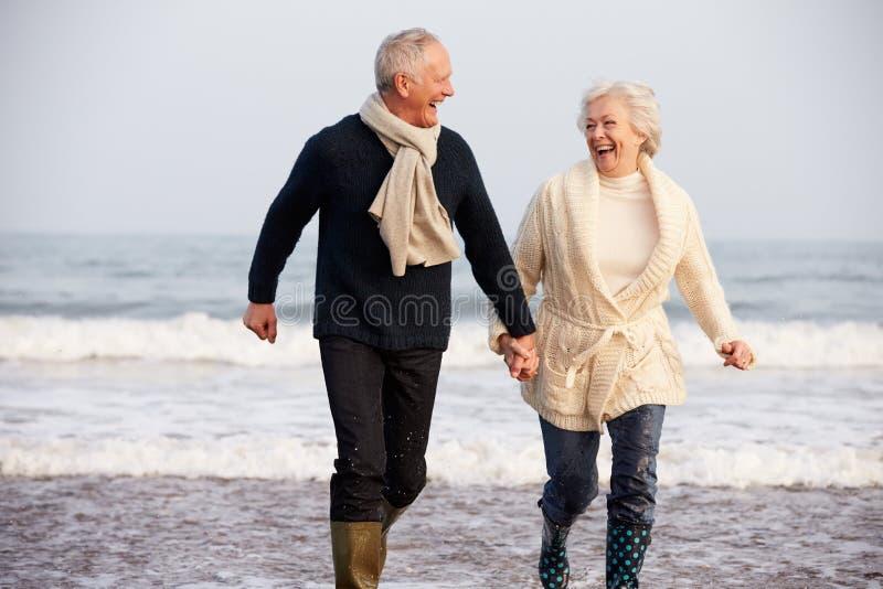 Senior Couple Running Along Winter Beach stock images