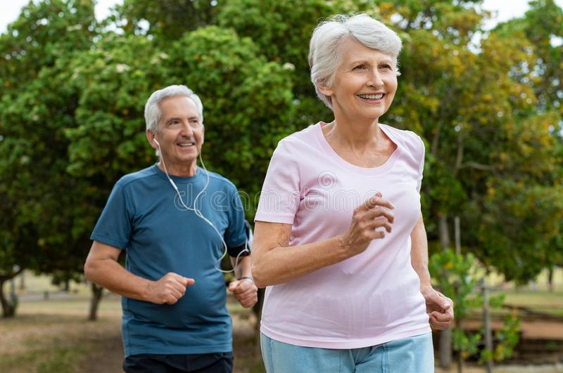 Senior couple running outdoor royalty free stock images