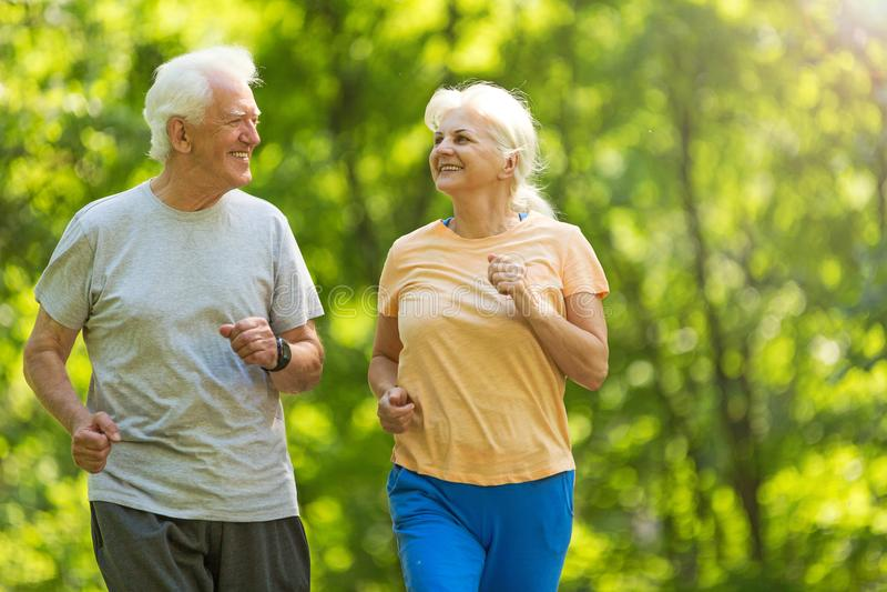 Senior couple running in park. Smiling happy elderly seniors couple stock photo