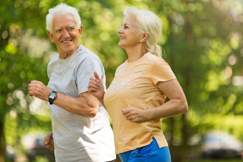 Senior couple running in park. Smiling happy elderly seniors couple stock images