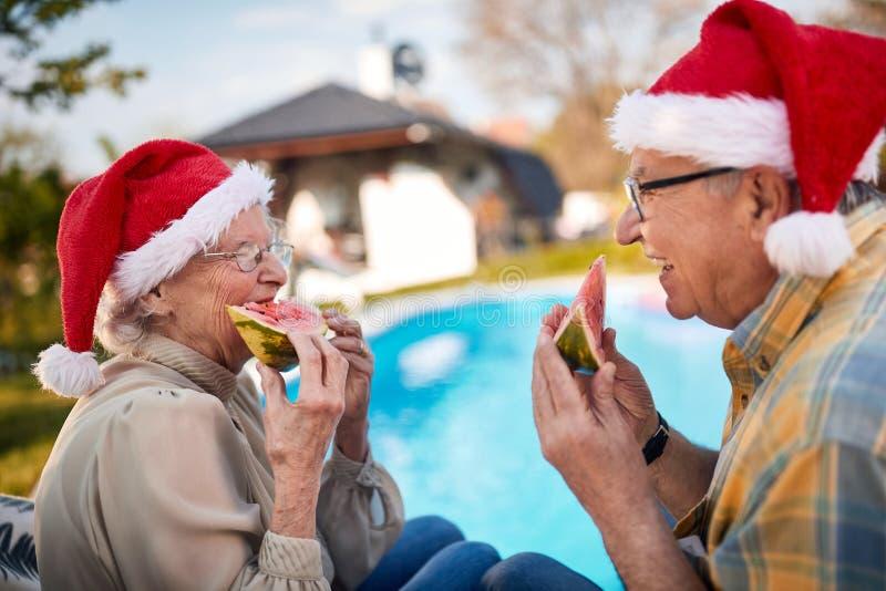 Senior couple in Santa hats enjoy on Christmas holiday and eating watermelon royalty free stock photo