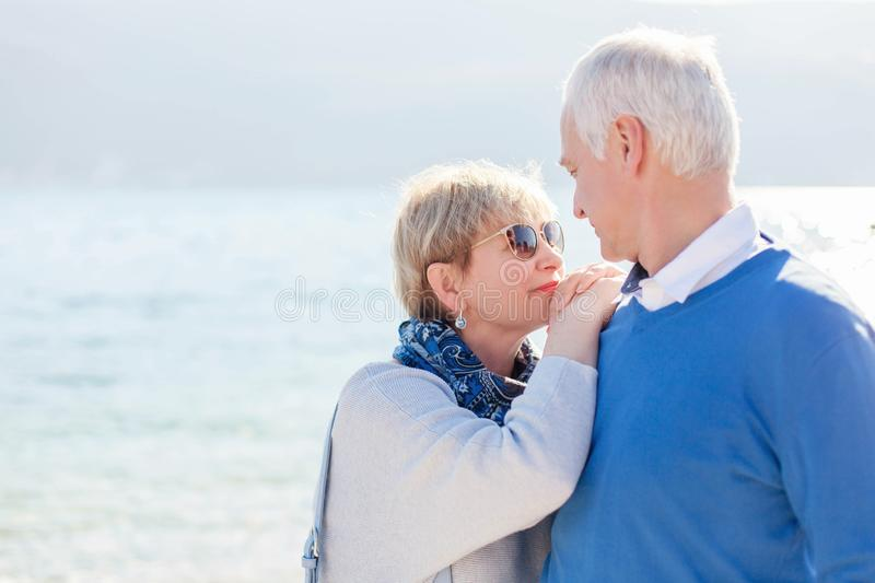 Senior couple at sea beach outdoor. Happy man and woman are hugging, embracing, enjoying retirement and life. royalty free stock images