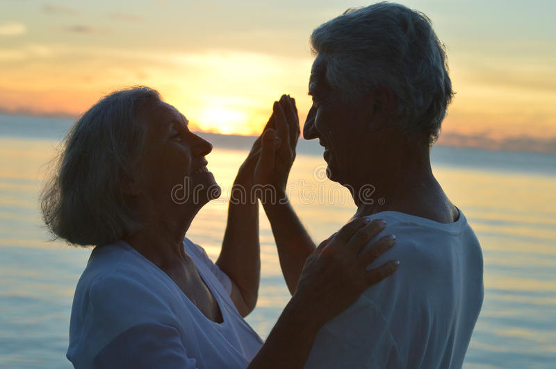 Senior couple at sea at sunset stock images