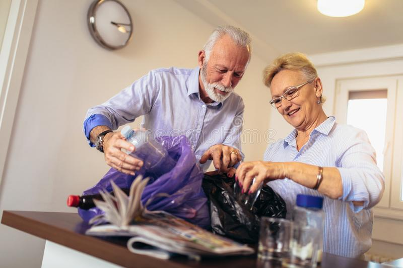 Senior couple separating recyclable trash. At home royalty free stock photo