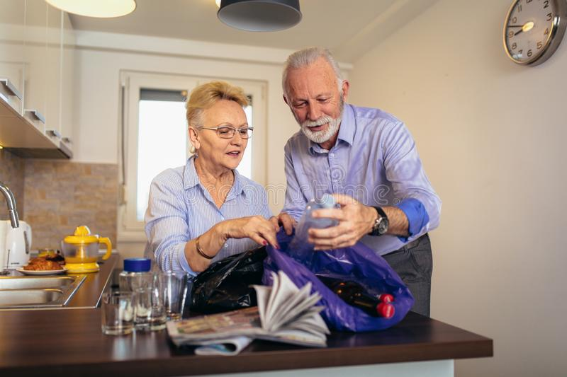 Couple separating recyclable trash at home. Senior couple separating recyclable trash at home stock image