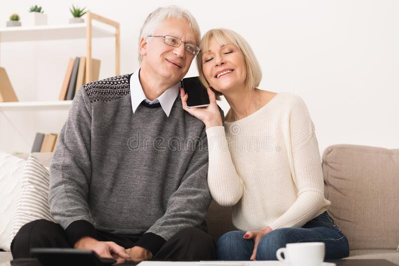 Senior couple sharing smartphone, having phone call royalty free stock photo