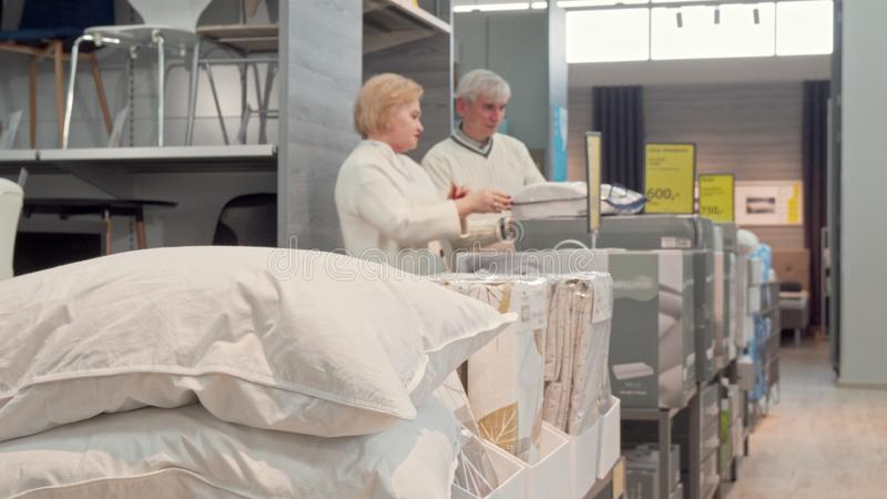 Senior couple shopping for new comfortable sleep pillows at furnishings store. Selective focus on a pillow, elderly customers examining orthopedic pillows on stock image
