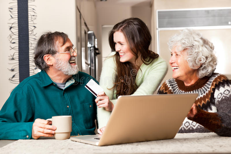 Senior couple shopping online. A portrait of a happy senior couple shopping online with the help from their granddaughter stock images