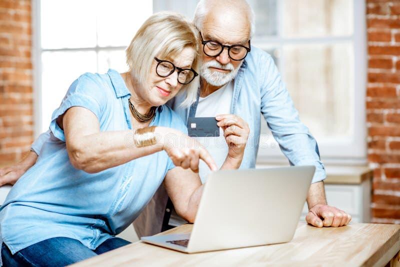 Senior couple shopping online. Happy senior couple shopping online using credit card and laptop at home stock image