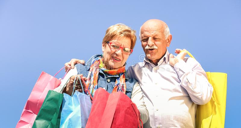Senior couple shopping together with wife watching in husband bags - Elderly concept with mature man and woman having fun. On sunny day - Happy retired people stock photos