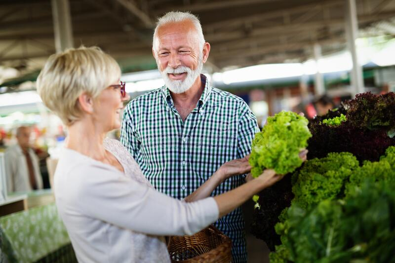 Mature couple shopping vegetables and fruits on the market. Healthy diet. stock photography